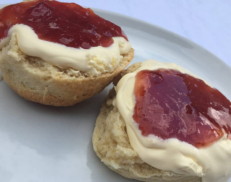 Scone cut in half with clotted cream and strawberry jam