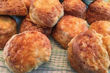 group of cheese scones laid out on a tea towel on a table